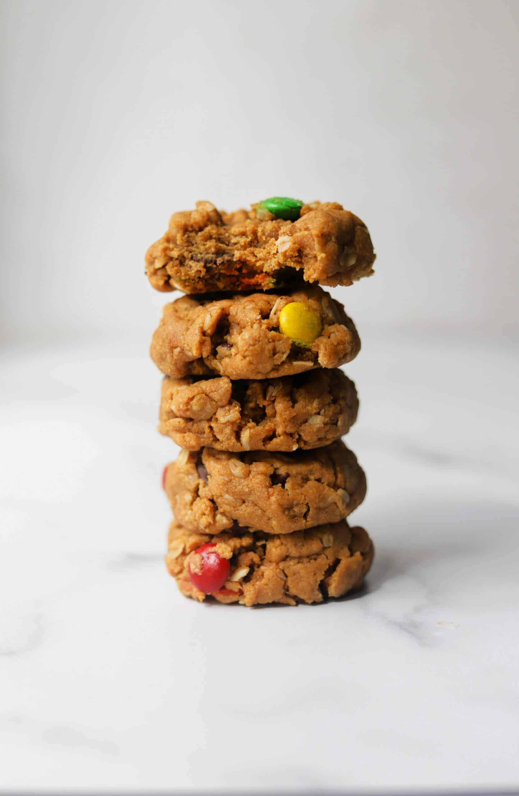 Monster cookies stacked on parchment paper.