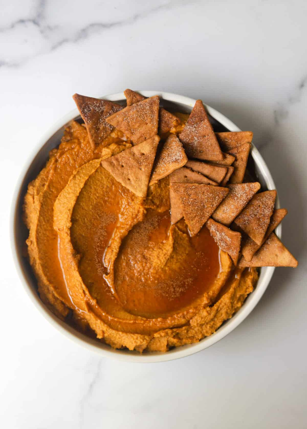A white dish filled with pumpkin pie hummus lined with cinnamon pita chips.
