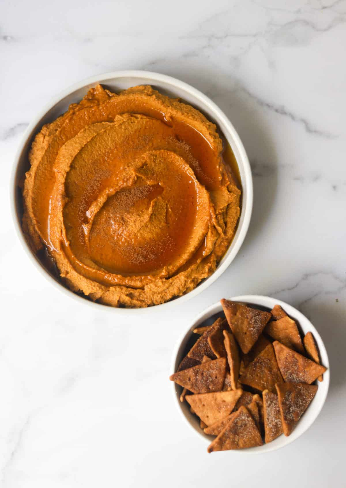 A birds eye view of a white dish filled with pumpkin pie hummus and a small dish with cinnamon pita chips.